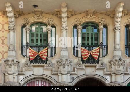Drapeaux nationaux catalans placés sur les balcons français des caisses Ramos à Barcelone, Catalogne, Espagne. Le bâtiment conçu par l'architecte moderniste catalan Jaume Torres i Grau a été construit entre 1906 et 1908 sur la Plaça de Lesseps (Plaza de Lesseps).