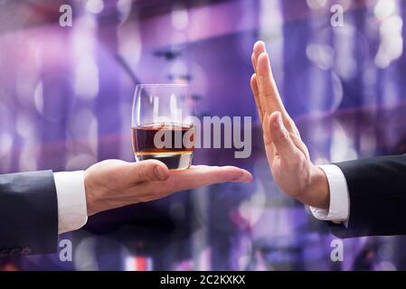 Close-up of Businessman part rejetant verre de Whisky offert par l'entrepreneur contre l'arrière-plan lumineux Banque D'Images