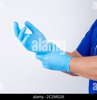 Médecin homme en uniforme bleu met ses mains Gants latex stériles blanc avant une chirurgie, fond blanc Banque D'Images