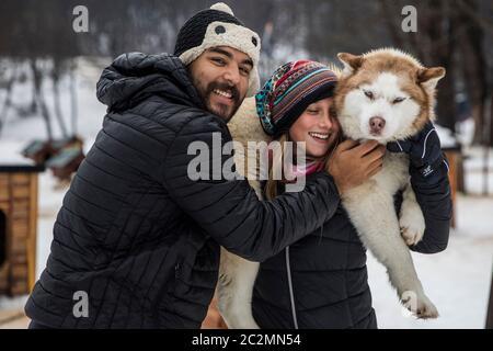 couple transportant un chien sibérien en hiver entouré de neige. Banque D'Images