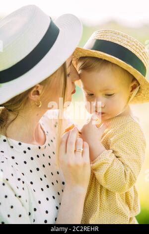 Portrait de mère avec sa fille en chapeaux tout en marchant dans le parc.