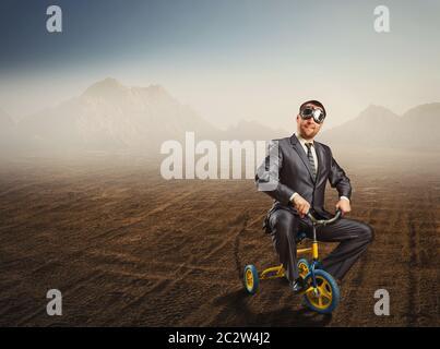 Étrange businessman riding un petit vélo contre l'arrière-plan du désert
