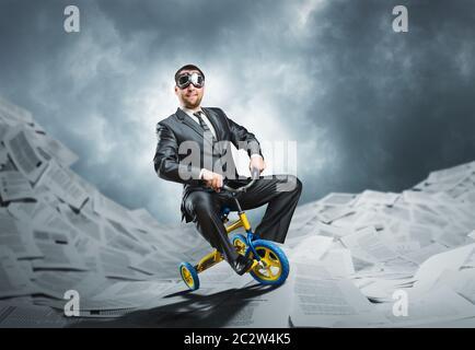 Étrange businessman riding un petit vélo contre papier fond