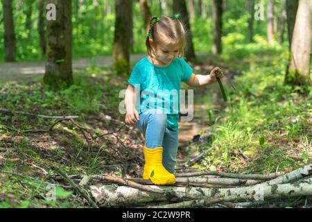 une petite fille marche à travers des flaques dans des bottes en caoutchouc dans la forêt