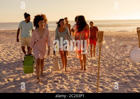 Groupe d'amis de course mixte marchant sur la plage Banque D'Images