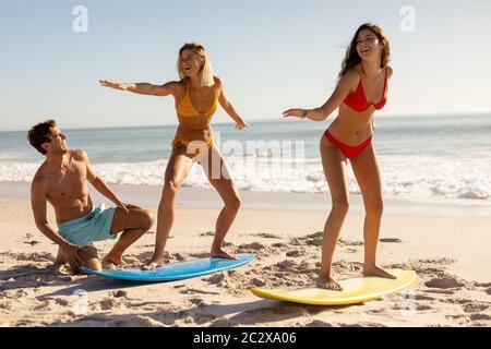 Groupe d'amis de race blanche surfant sur la plage Banque D'Images