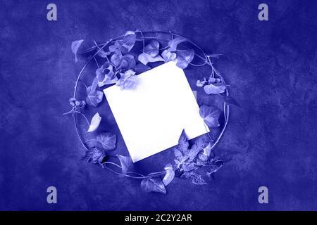Modèle de carte de vœux ou d'invitation avec une couronne de feuilles et de fleurs placées, photo au-dessus avec espace pour les copies. Ivy et Banque D'Images