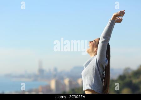 Profil d'une femme excitée soulevant des bras pour célébrer le succès à l'extérieur dans la périphérie de la ville
