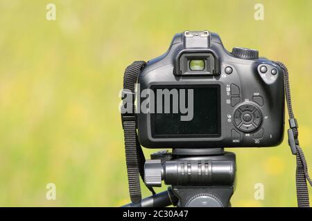 Appareil photo reflex numérique Canon sur trépied sur fond bokeh vert Banque D'Images