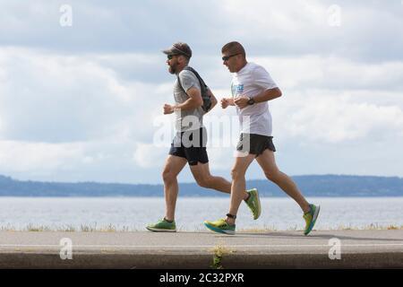 Deux hommes courent le long de la piste Alki un après-midi ensoleillé à Seattle, Washington. Banque D'Images