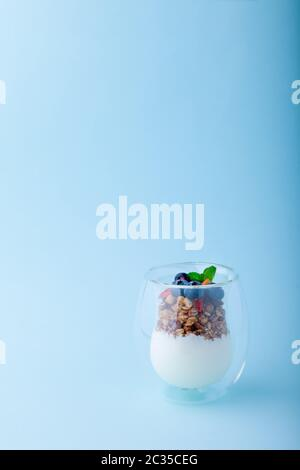 Yaourt biologique grec naturel blanc et granola aux baies fraîches, fraises, bleuets, menthe en verre transparent sur fond bleu, gros plan, Banque D'Images