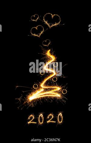Résumé de l'arbre de Noël étincelante de la foudre avec des boules de noël et paillettes en forme de coeur isolé sur fond noir. Noël magique. PF2020.