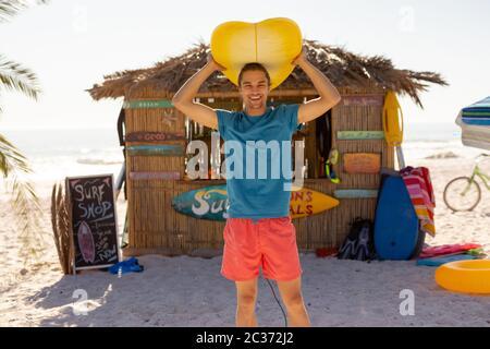 Homme caucasien tenant une planche de surf sur la plage
