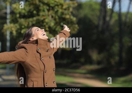 Heureux woman wearing jacket outstretching bras dans un parc en hiver