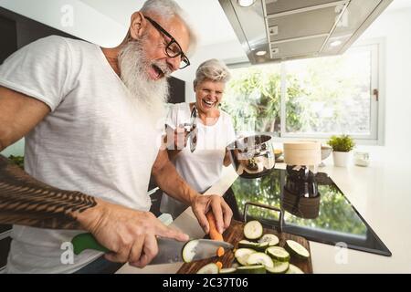 Couple senior heureux ayant plaisir à cuisiner ensemble à la maison - personnes âgées préparant un déjeuner santé dans la cuisine moderne Banque D'Images