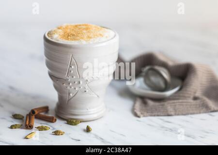 Une tasse de chai Latte avec du sucre de canne sur le dessus. Sur une table en marbre avec fond blanc. Il y a quelques gousses de cardamome et des bâtons de cannelle à côté de la merde