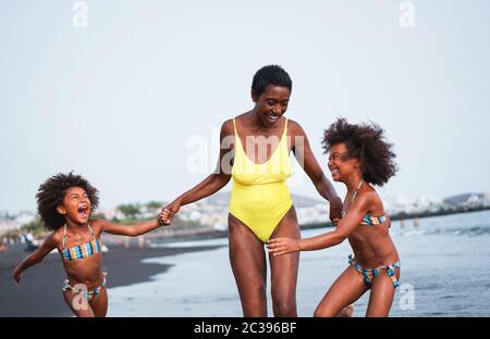Frères jumeaux qui coure sur la plage avec une mère souriante - des familles noires qui s'amusent l'été - vacances, voyages et vie de bonheur Banque D'Images