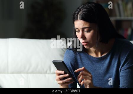 Une femme inquiète à vérifier le texte du téléphone portable assis sur un canapé dans la nuit à la maison dans la nuit Banque D'Images
