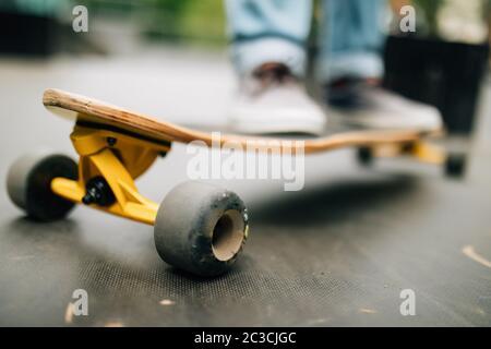 Gros plan sur un jeune homme méconnu qui fait du surf en plein air dans un parc de skateboard, espace de copie