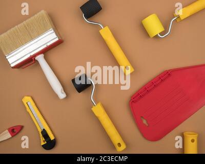 Un outil de peinture pour le papier peint. Arrière-plan beige. Vue du dessus. Le concept de réparation.