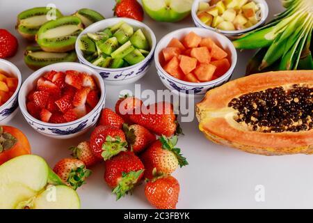 Faire une salade de fruits colorée à base de pomme, de papaye, de fraise, de kiwi et d'ananas. Banque D'Images