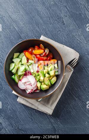 Bol de bouddha vegan. Salade végétarienne saine avec tomates cerises, concombre, radis, avocat, laitue Banque D'Images