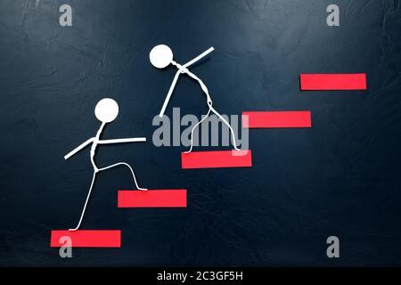 Aider la main, soutenir et travailler en équipe. Deux figurines en bâton grimpant sur une échelle rouge.