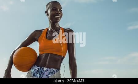 Femme en forme de sport porter debout à l'extérieur tenant un basket-ball. Une joueuse de basket-ball qui regarde loin et sourit contre le ciel.