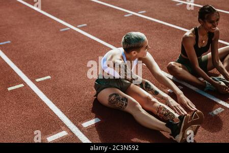 Deux athlètes féminins effectuant des exercices d'étirement assis sur la piste de course. Femme coureurs assis sur la piste de course étirant les jambes.