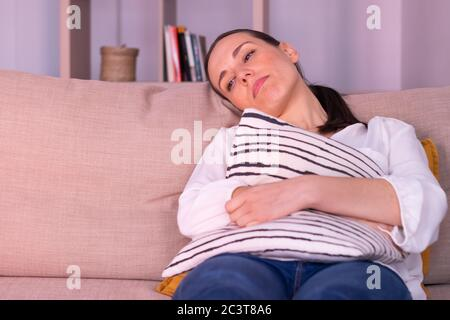 Jeune femme de brunette ennuyé seule assise sur le canapé à la maison embrassant un coussin. Elle porte une chemise blanche et une queue de cheval. Banque D'Images