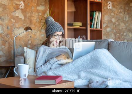 J'ai surpris une jeune femme assise sur le canapé à la maison, regardant l'écran d'un ordinateur portable. Elle porte un chapeau de laine et des lunettes. Image horizontale.