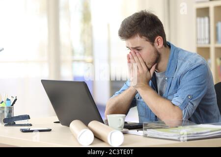 Un entrepreneur inquiet qui regarde un ordinateur portable se plaint assis au bureau Banque D'Images