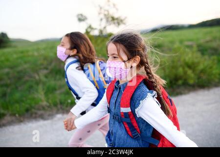 Deux petites filles en voyage à l'extérieur dans la nature, portant des masques faciaux.