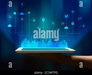 Tablette de main avec hologramme de ville urbaine, fond bleu