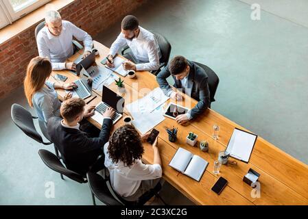 Équipe d'affaires multiraciale travaillant assis à la table au bureau, à angle élevé