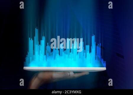 Tablette numérique portable avec ville futuriste holographique, fond bleu