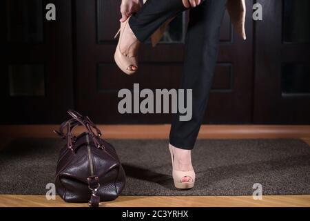 une femme fatiguée rentre à la maison, jette son sac, prend inlassablement ses chaussures et entre dans la maison Banque D'Images