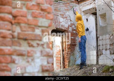 Un jeune homme dessine de la peinture en aérosol sur le mur d'un bâtiment abandonné
