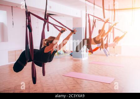 Belles jeunes filles faisant du yoga à la mouche sur des hamacs, un mode de vie sain Banque D'Images