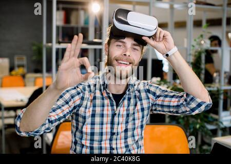 Entreprise, personnel, vision 3d et concept de réussite. Joyeux homme d'affaires barbu souriant dans un maillot à carreaux décontracté, s'amusant lors des tests de la nouvelle vr 3d