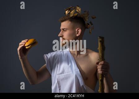Un jeune homme sous le couvert d'un dieu olympique dans une vignette de Laurier avec un personnel, tient un cambrioleur dans la main, le regardant. Photo de studio sur un gris Banque D'Images