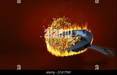 Délicieux riz frit chinois sauté dans un poêle chaud et jeté dans l'air avec du poulet, des poivrons, des petits pois, des carottes et des oignons. Montée de vapeur et Banque D'Images