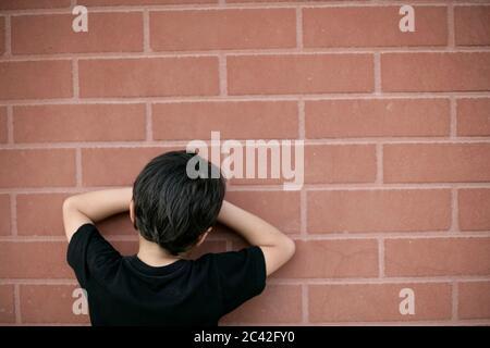 Le petit garçon compte sur le mur pour se cacher - la jeunesse - l'enfance