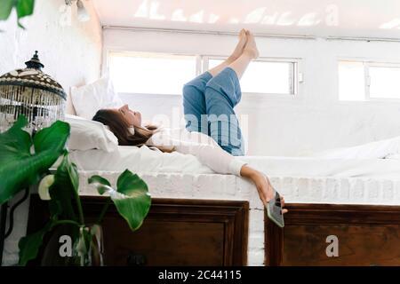 Femme souriante couchée au lit, écoutant de la musique avec un casque et un téléphone portable