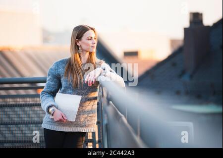 Jeune femme attentionnée tenant un ordinateur portable tout en se tenant sur la terrasse du bâtiment en ville
