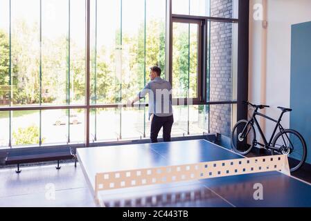 Homme d'affaires debout dans le bureau de loft, vue par la fenêtre