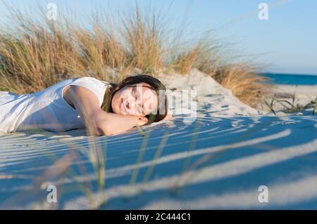 Portrait de femme souriante avec les yeux fermés se détendre sur la plage, Sardaigne, Italie