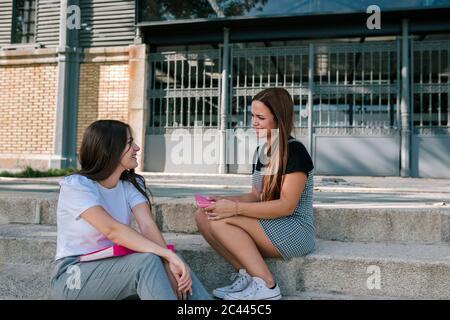 Souriant, de jeunes amies parlent tout en étant assise sur les marches du campus universitaire Banque D'Images