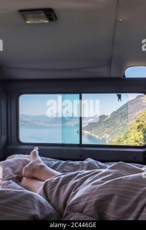 La Suisse, Lucerne, Schwyz, les pieds nus de personne dormant à l'intérieur de motor home avec le lac des Quatre-Cantons vu à travers la vitre Banque D'Images