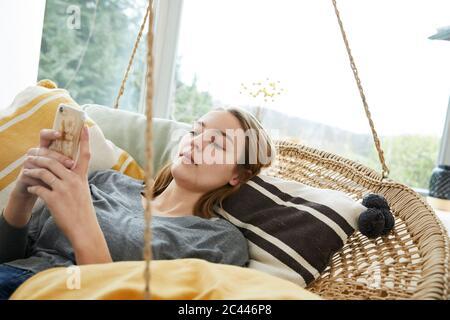 Portrait d'une jeune femme allongé sur un balancement à la maison à l'aide d'un smartphone Banque D'Images